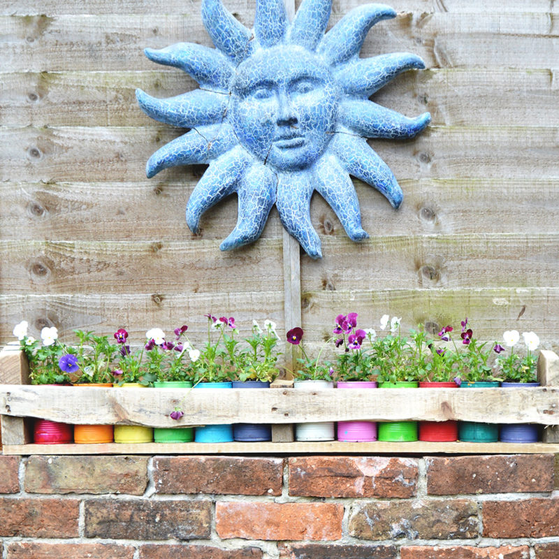 Upcycled colorful tin can planters with a handy pallet trough.