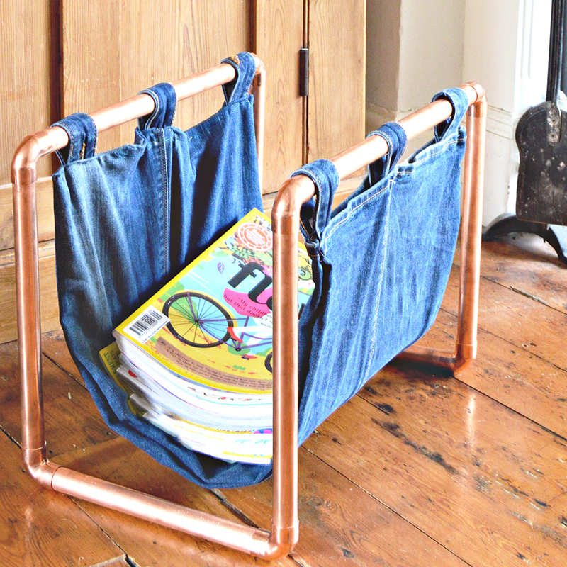 By upcycling a pair of old jeans and some copper piping, you can make this on-trend denim and copper DIY magazine rack.