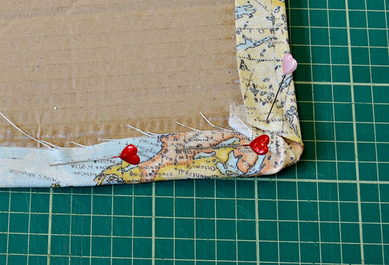 pinning the fabric to the cardboard