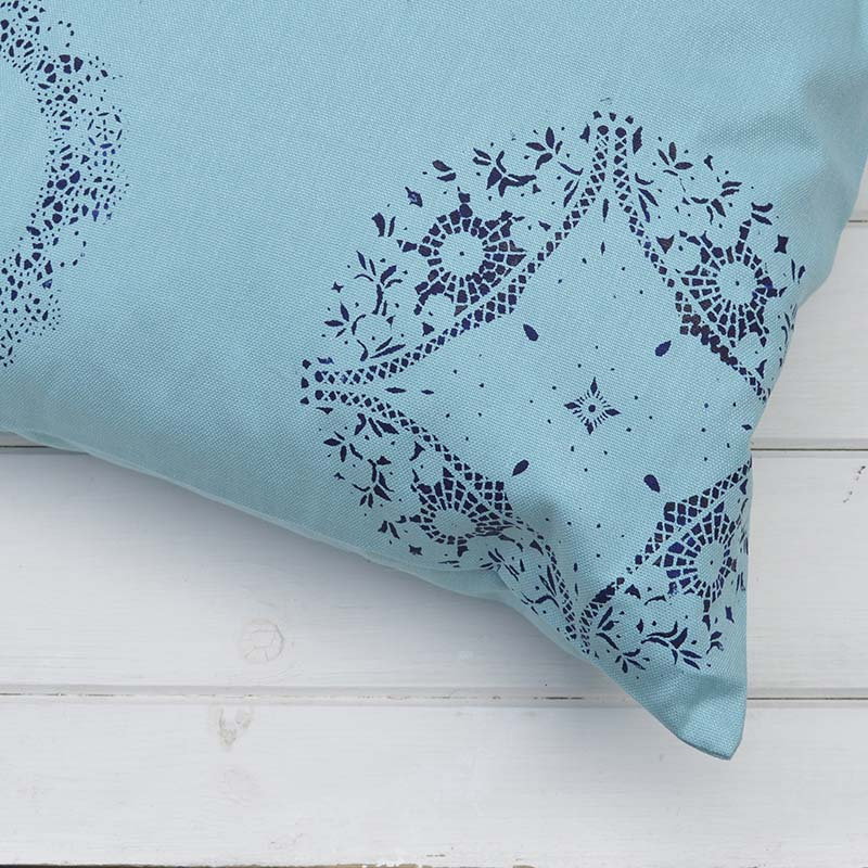 Brighten up your cushions by painting them using a doily as a stencil