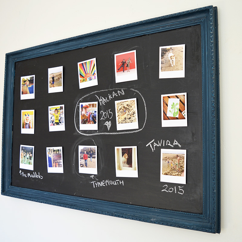 Upcycled old art into chalkboard photo frame.  Use velcro sticky dots to easily move the photos around.