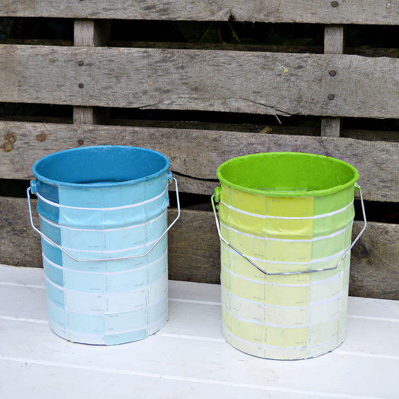 Empty paint cans upcycled with paint chips for colourful storage or planters.