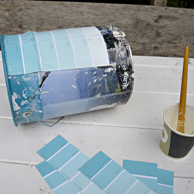 Upcycling empty paint cans by decoupaging with paint chips for an ombre effect