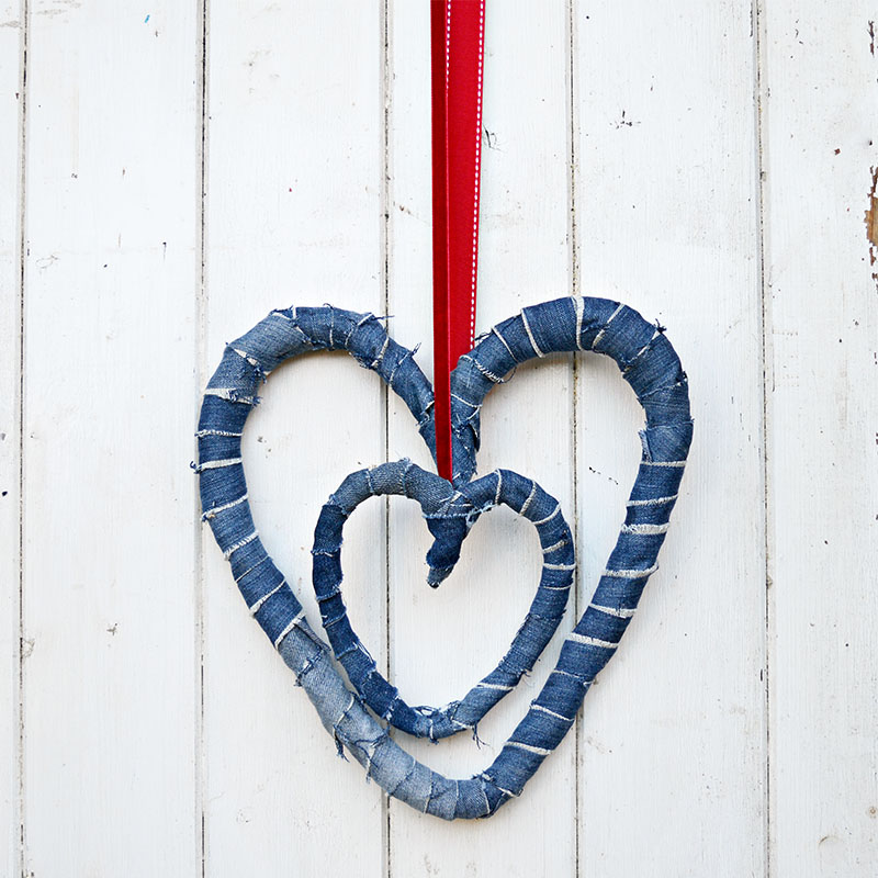 Use your old jeans and a coat hanger to make a gorgeous upcycled denim wreath for Valentines or all year round decor.