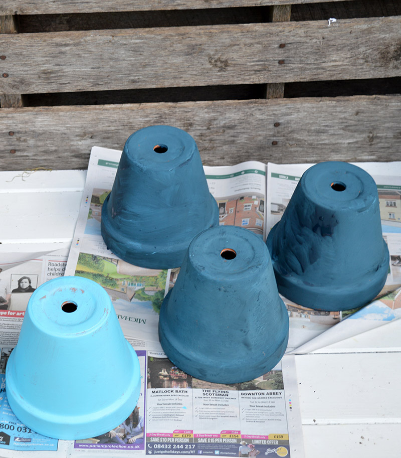 Blue painted terracotta pots for an outdoor wall planter.