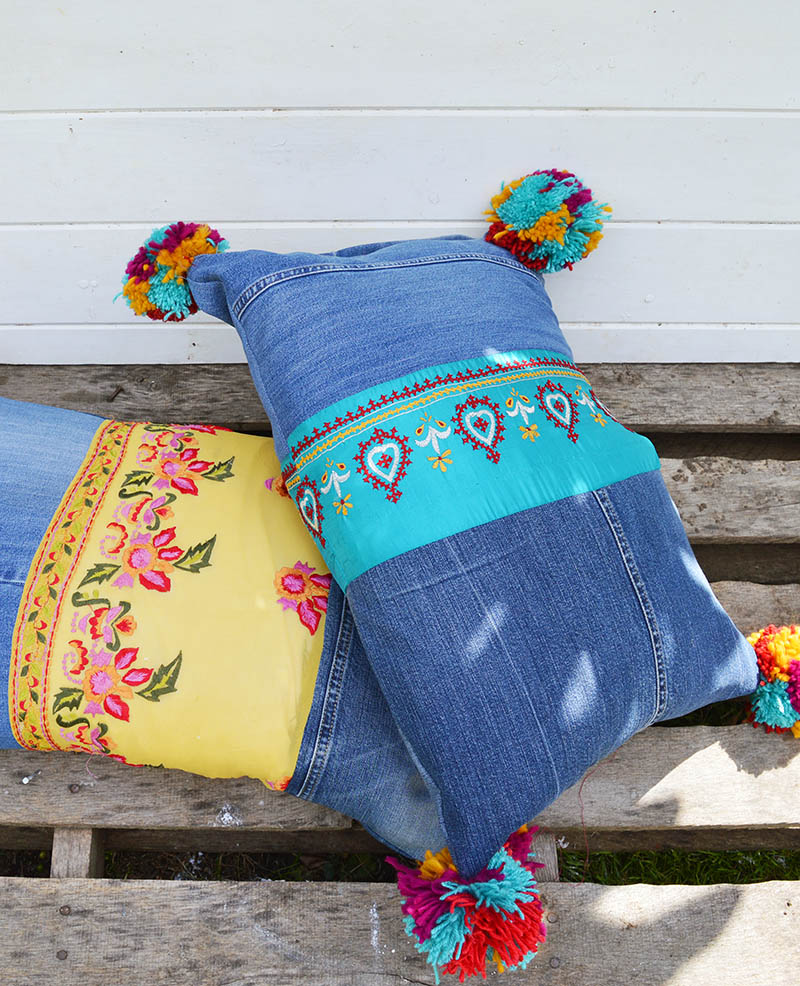 Finished upcycled boho jeans pillows with vintage sari trim and pom poms