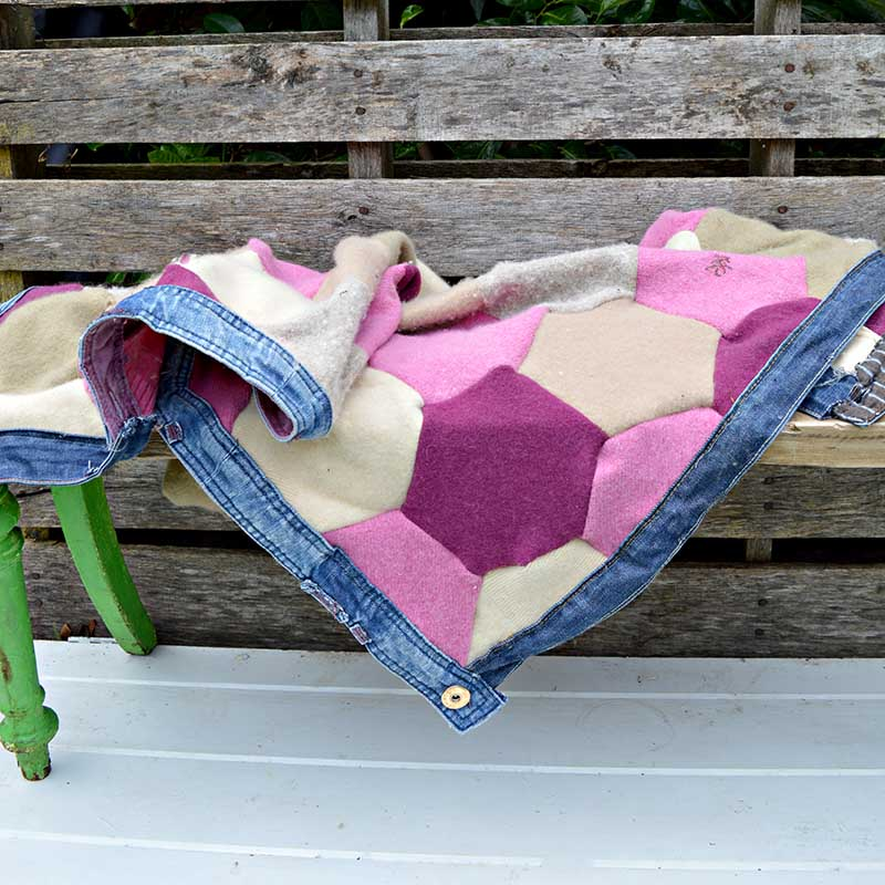 Upcycled sweater blanket made from felted wool jumpers and trimmed with recycled jeans waistbands.