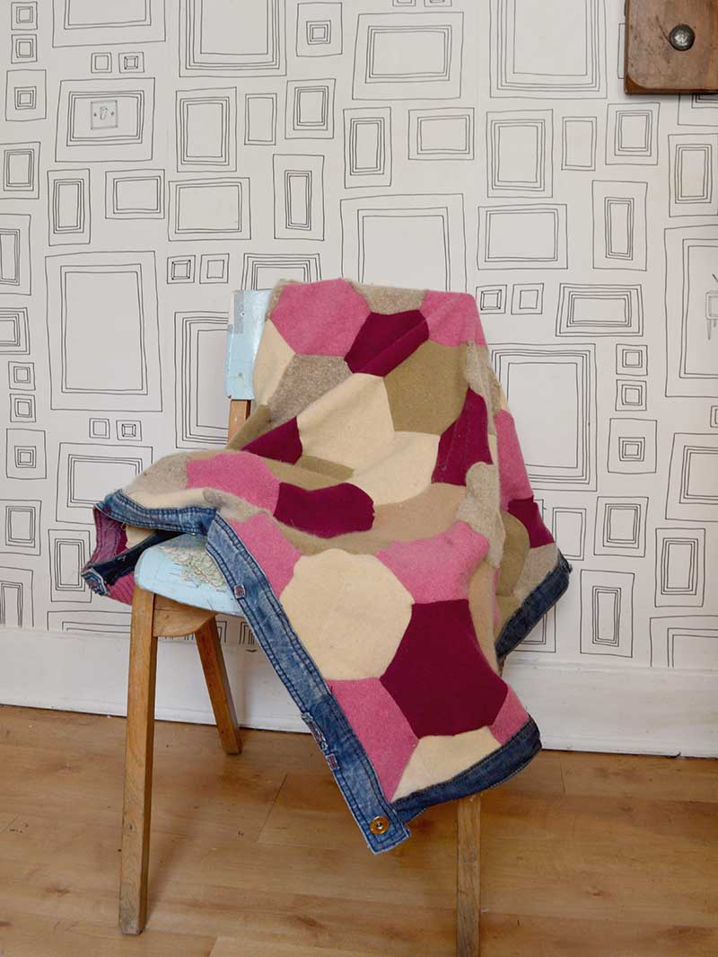 Full step by step tutorial to make a gorgeous hexagon patchwork upcycled sweater blanket complete with recycled denim waistband trim.