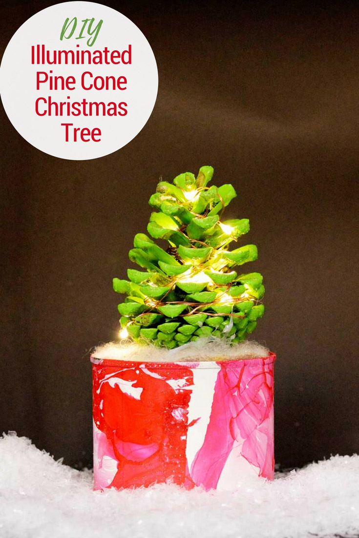 How to make a cute illuminated pine cone Christmas tree in a marble pot. This colorful Christmas tree complete with copper lights will brighten up any desk. #christmascrafts #christmas #pinecone #christmaslights