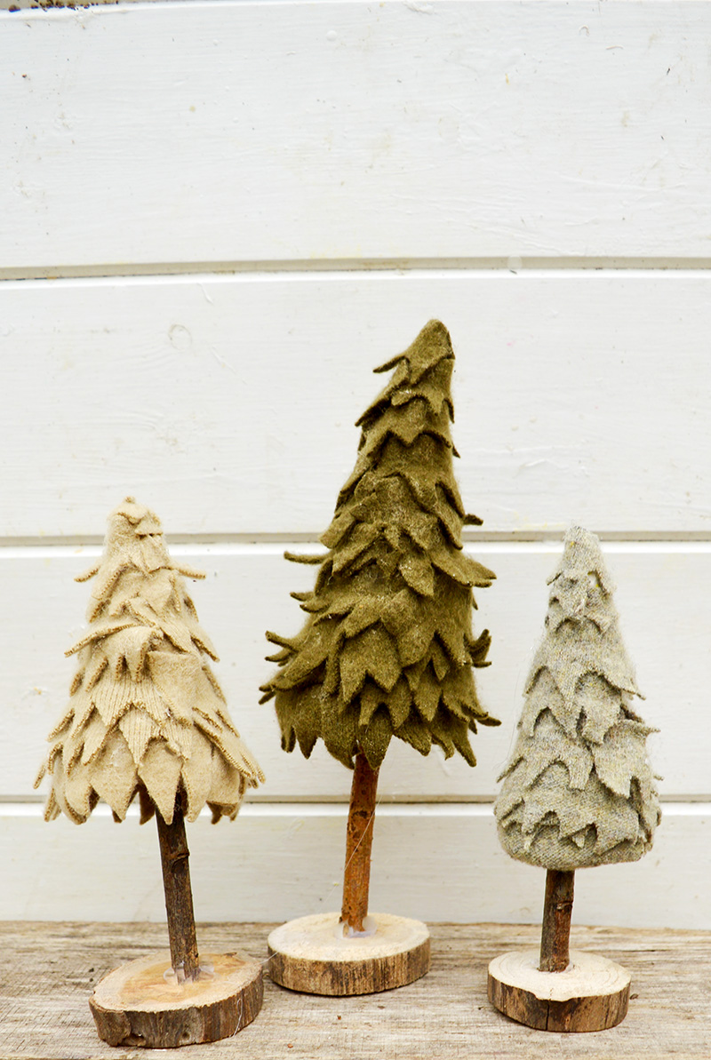 All you need is a cardboard tube a twig and some felt scraps to make these adorable felt Christmas trees.  So easy the kids can make them too!