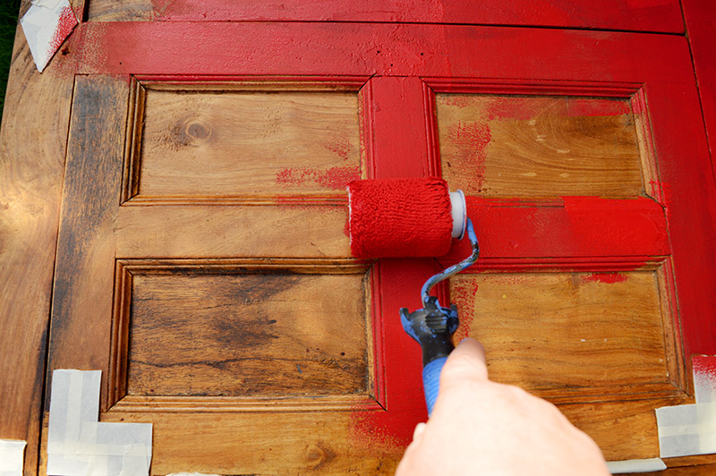 Painting a cabinet with a mini roller and chalk paint.