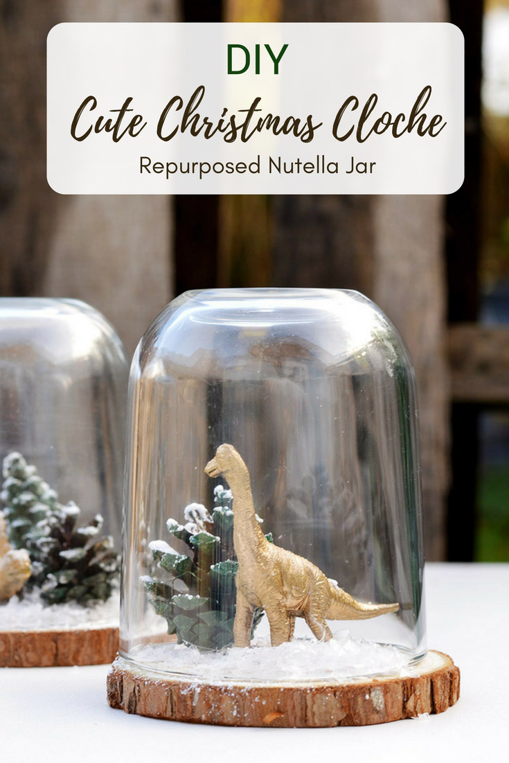 Add some fun to your Christmas decorations by repurposing a Nutella jar and making a super cute min Christmas Cloche (dinosaur terrarium). #christmascloche #snowglobe #dinosaurterrarium #christmasdecoration #glassdome
