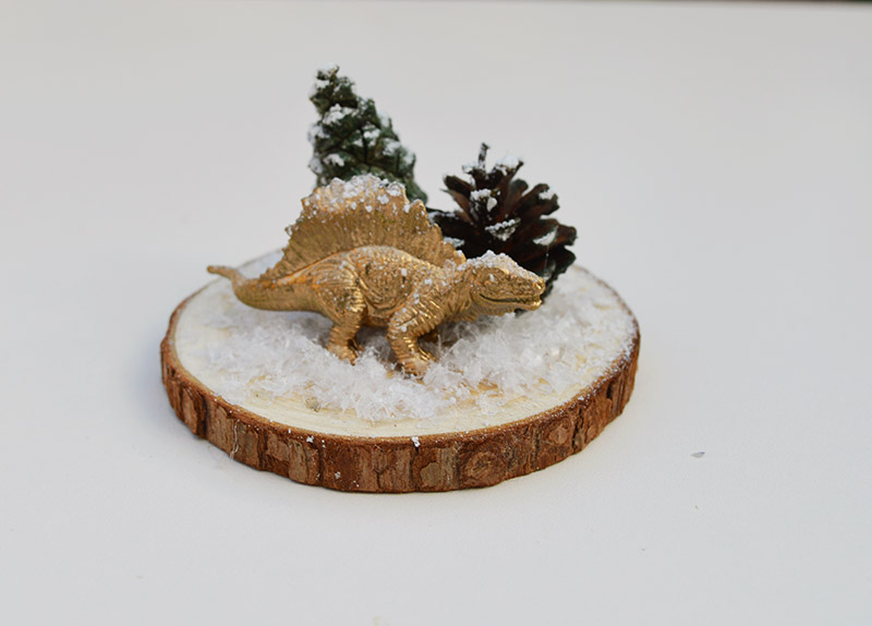 Glueing dinosaur and tree to woodslice for Christmas dinosaur terrarium