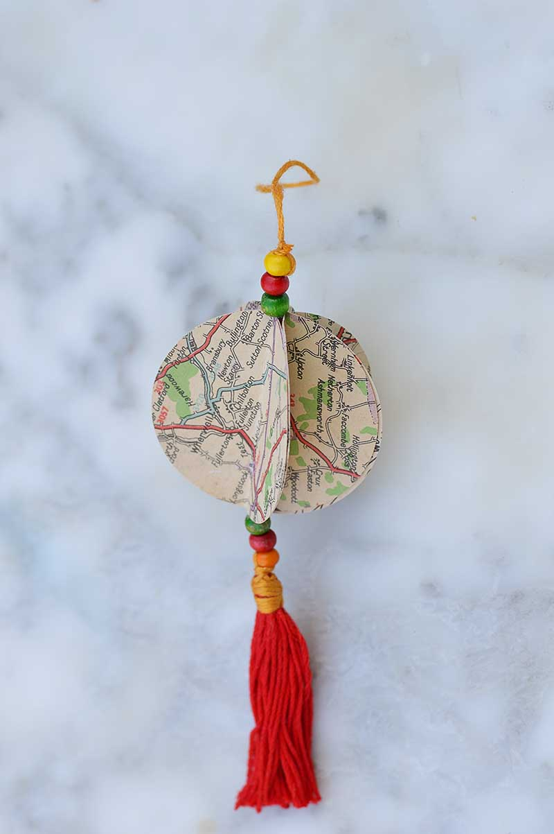 Repurpose old road maps to make a gorgeous map Christmas ornament complete with tassel.