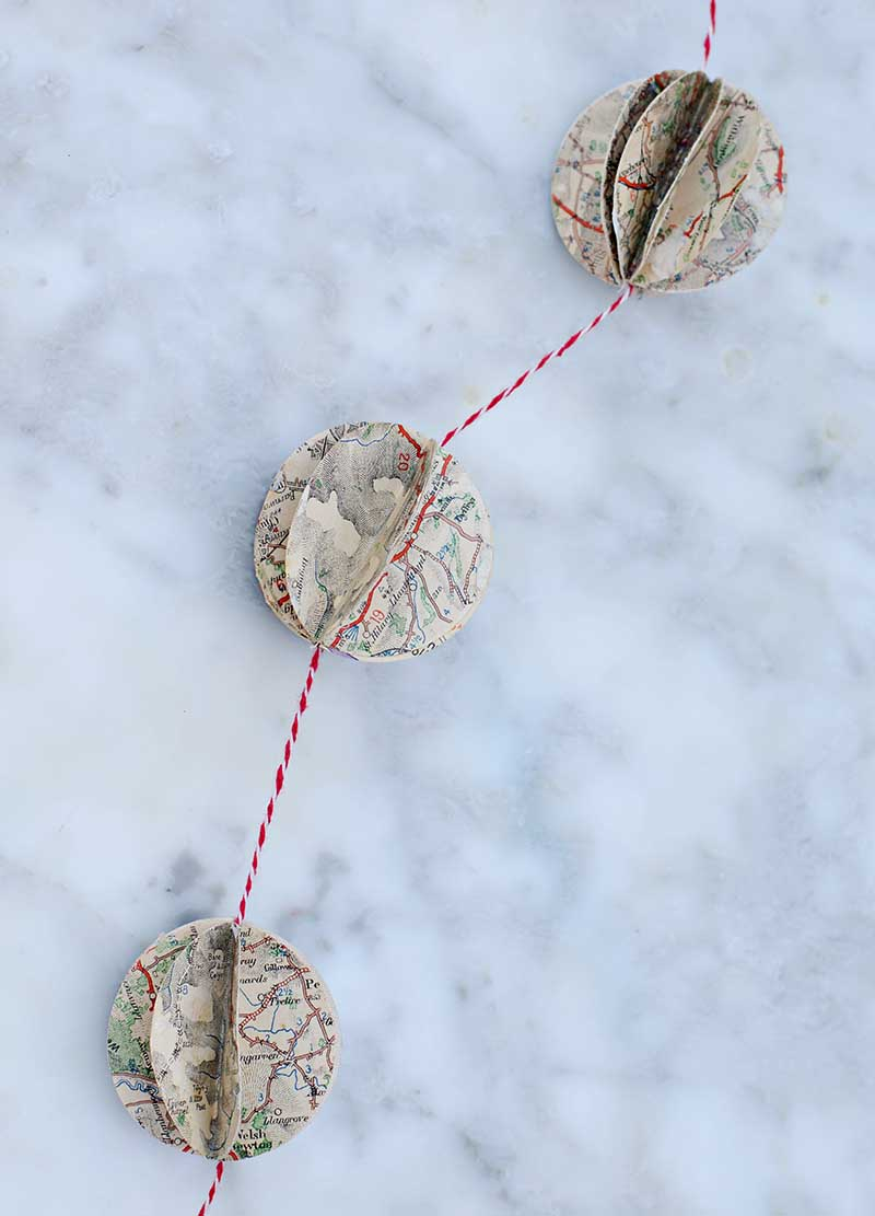 Upcycle old road maps to make a gorgeous DIY map decorations in the form of a garland.