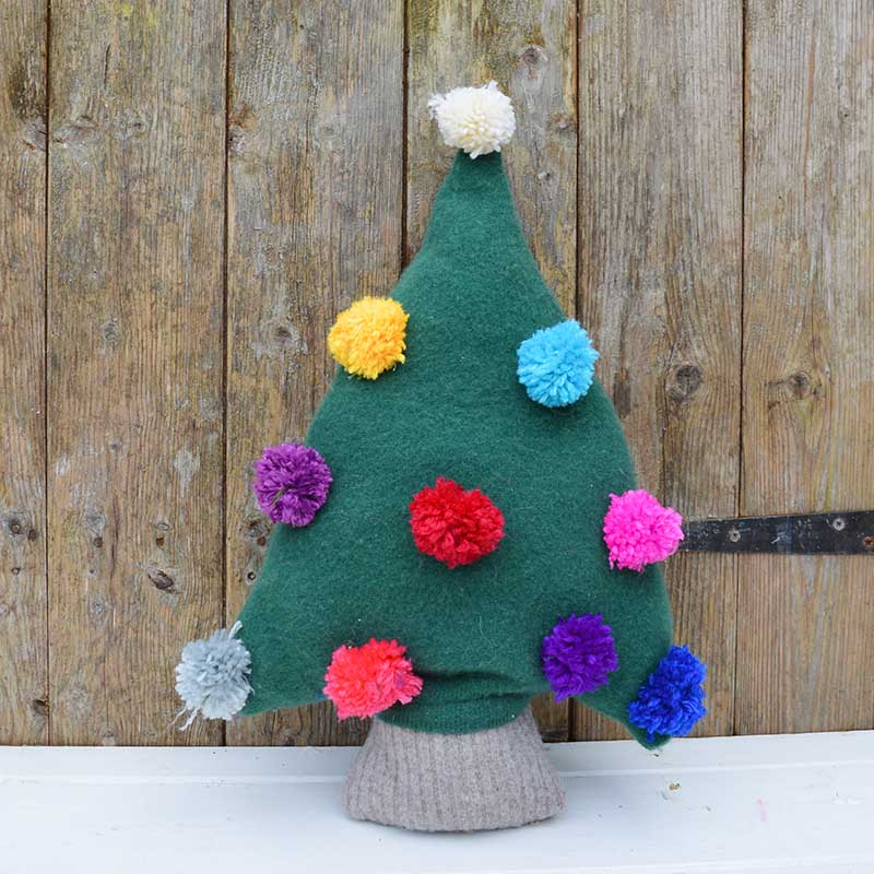 Make a really cute Christmas tree pillow from an old green sweater.  Add fun and colourful decorations to the sweater tree with pom poms.