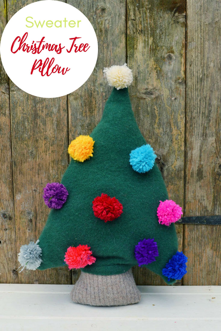 Make a really cute Christmas tree pillow from an old green sweater. Add fun and colourful decorations to the sweater tree with pom poms. #Christmascraft #sweater #Christmaspillow #repurposed #upcycle #pompom