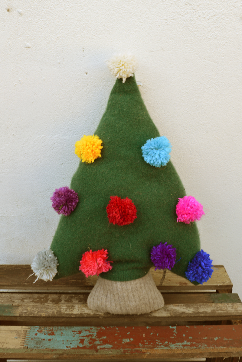 Upcycled sweater into a cute Christmas tree pillow with pom pom decorations.
