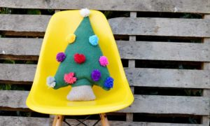 Repurpose an old sweater into a cute Christmas tree pillow with pom pom decorations