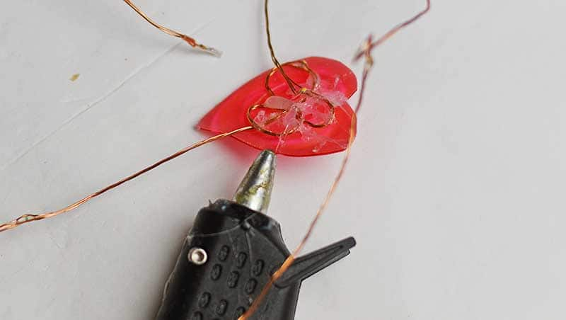 Gluing copper wire lights to the back of plastic hearts