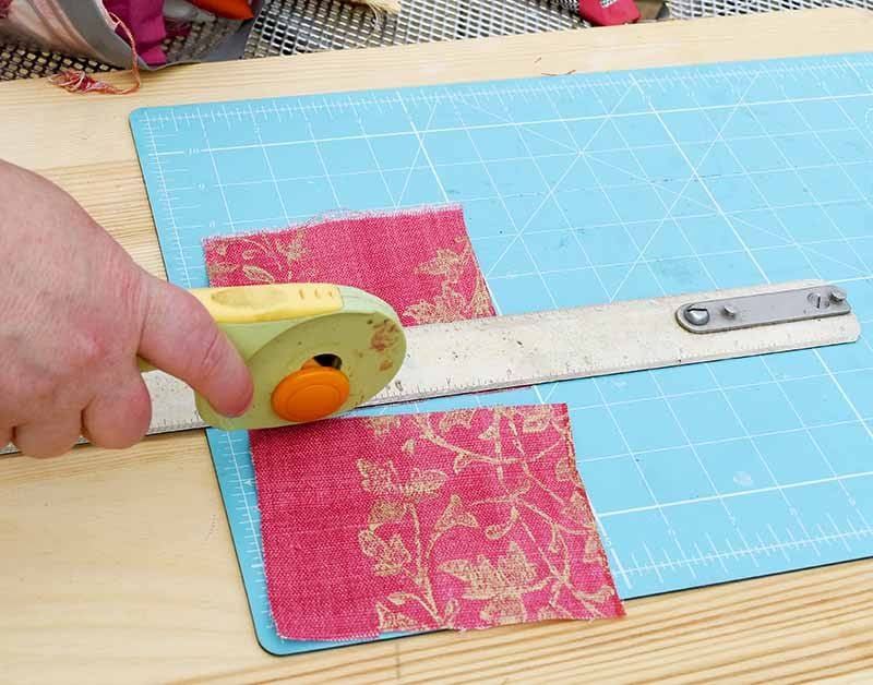 Cutting fabric scraps on mat