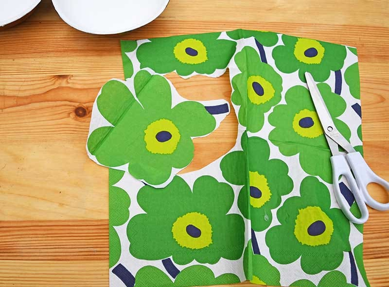 Cutting out Marimekko flower for decoupage on wood