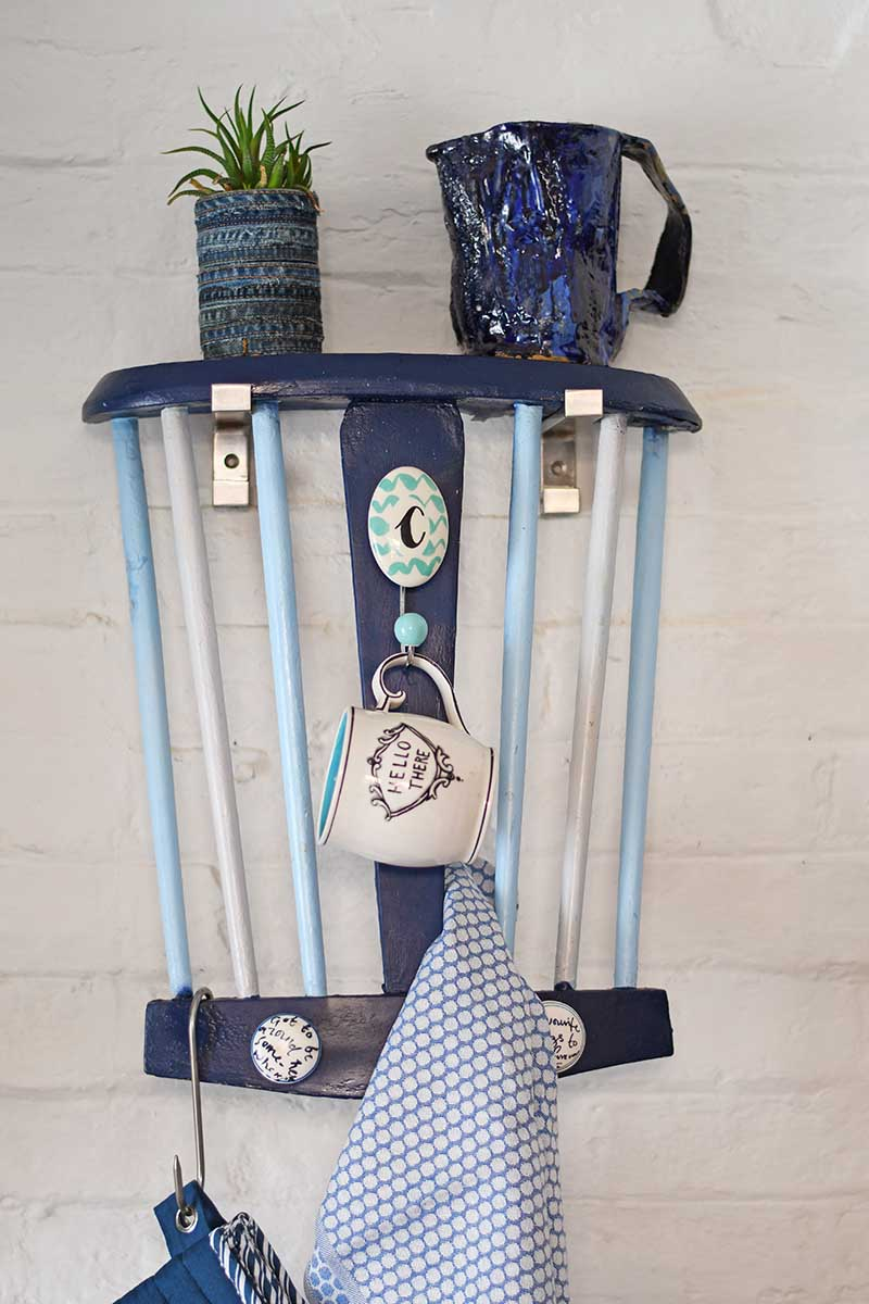 Repurposed Chair back into a handy kitchen towel rack and storage.