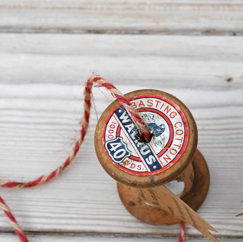 threading wooden spool with twine