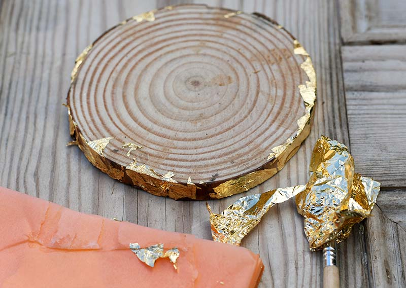 Adding gold leaf to wood slice bark