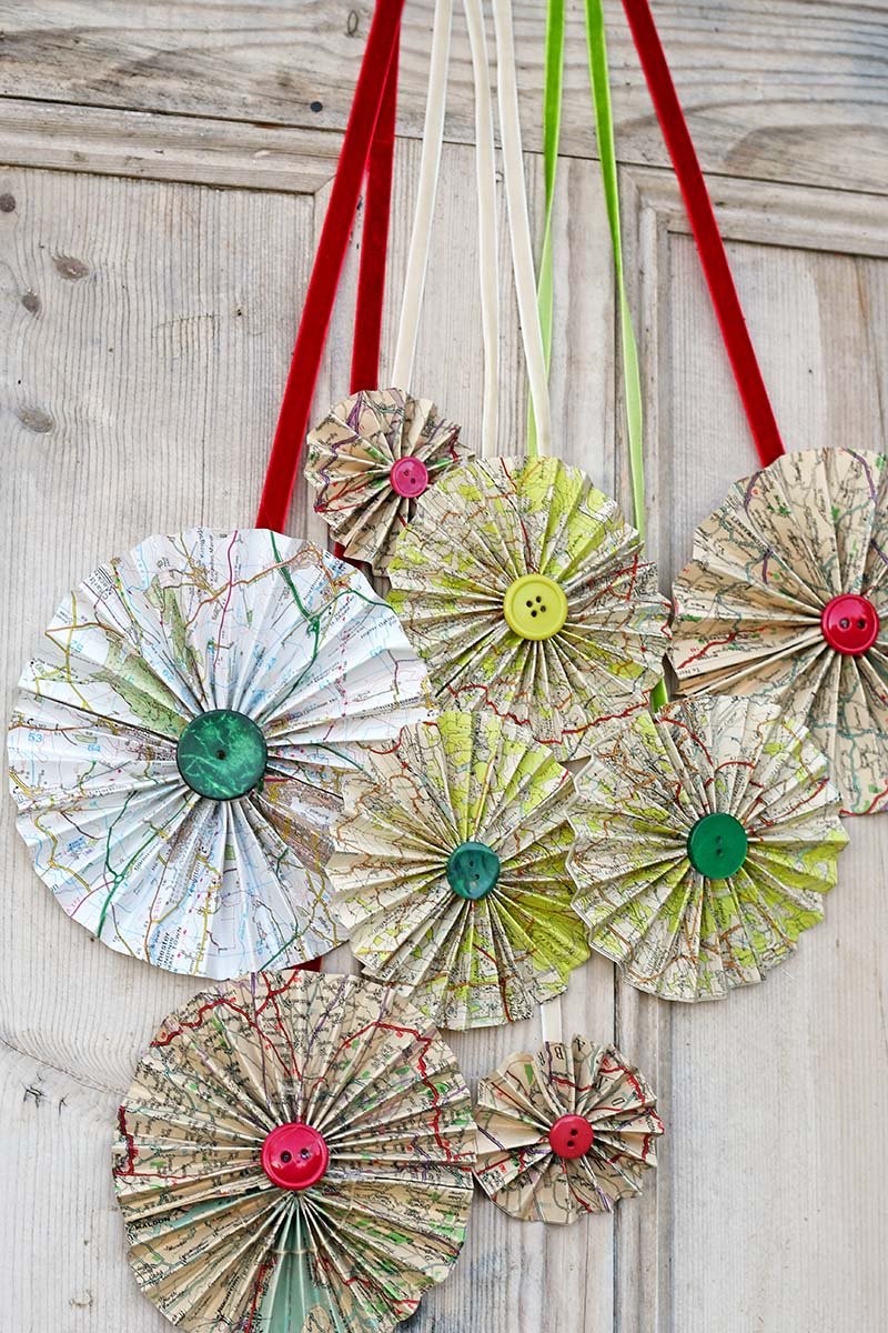 Hanging upcycled road map rosettes as a Christmas door decoration