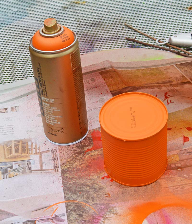 spray painting tin cans orange