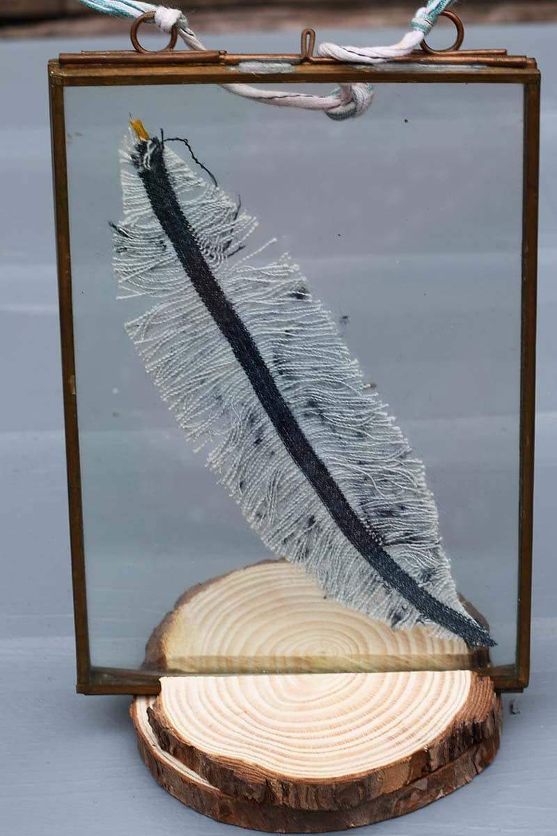 Feather in a photo frame on a wood slice stand