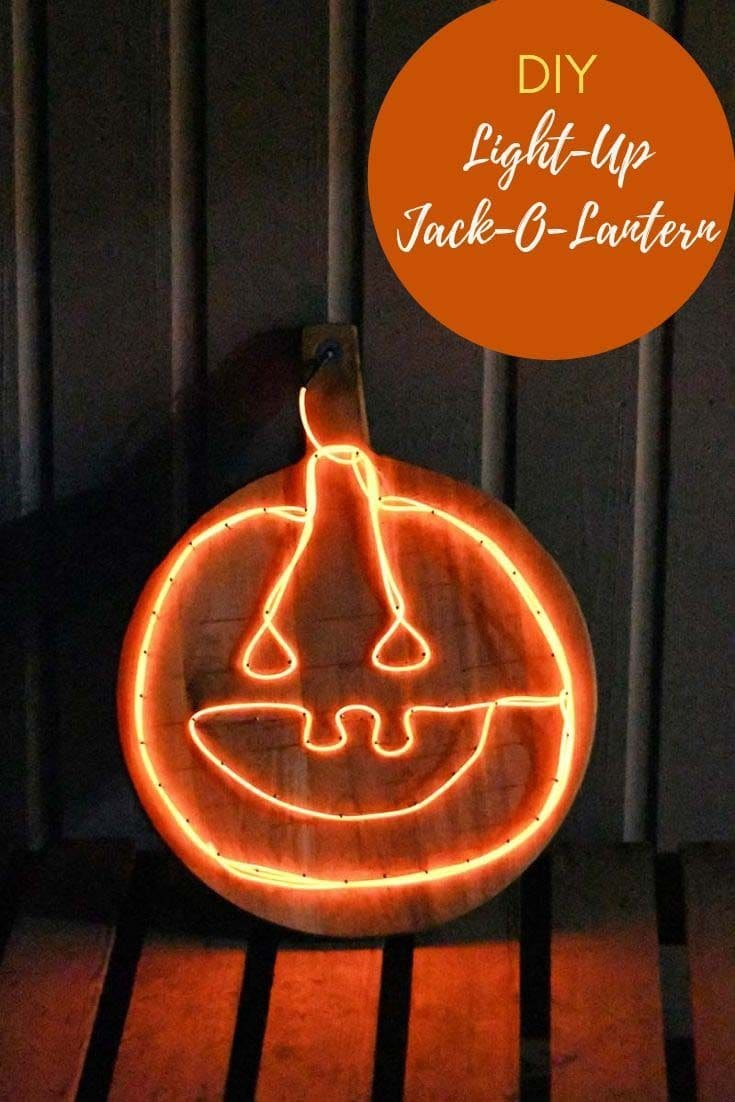 Upcycled chopping board into a fun illuminated Jack-O-Lantern sign.  A great affordable Halloween decoration for the porch.