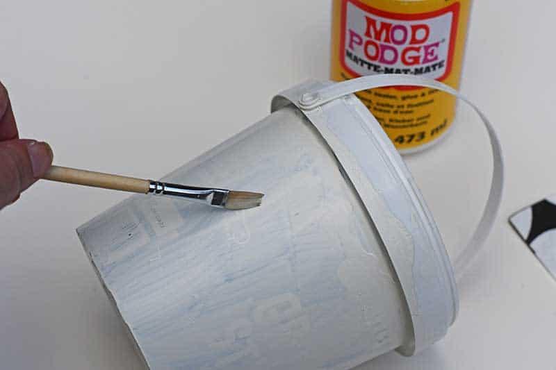 applying Mod Podge to hanging storage bucket.