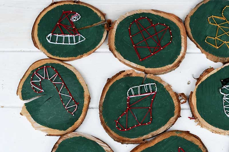String art ornaments on wood slices