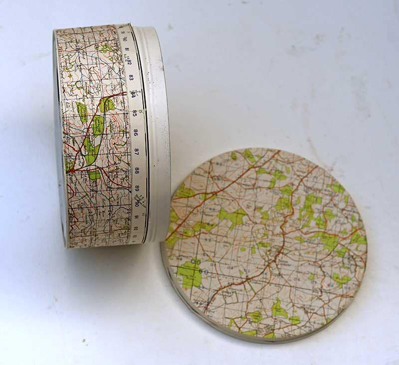 covering empty cookie tins with maps
