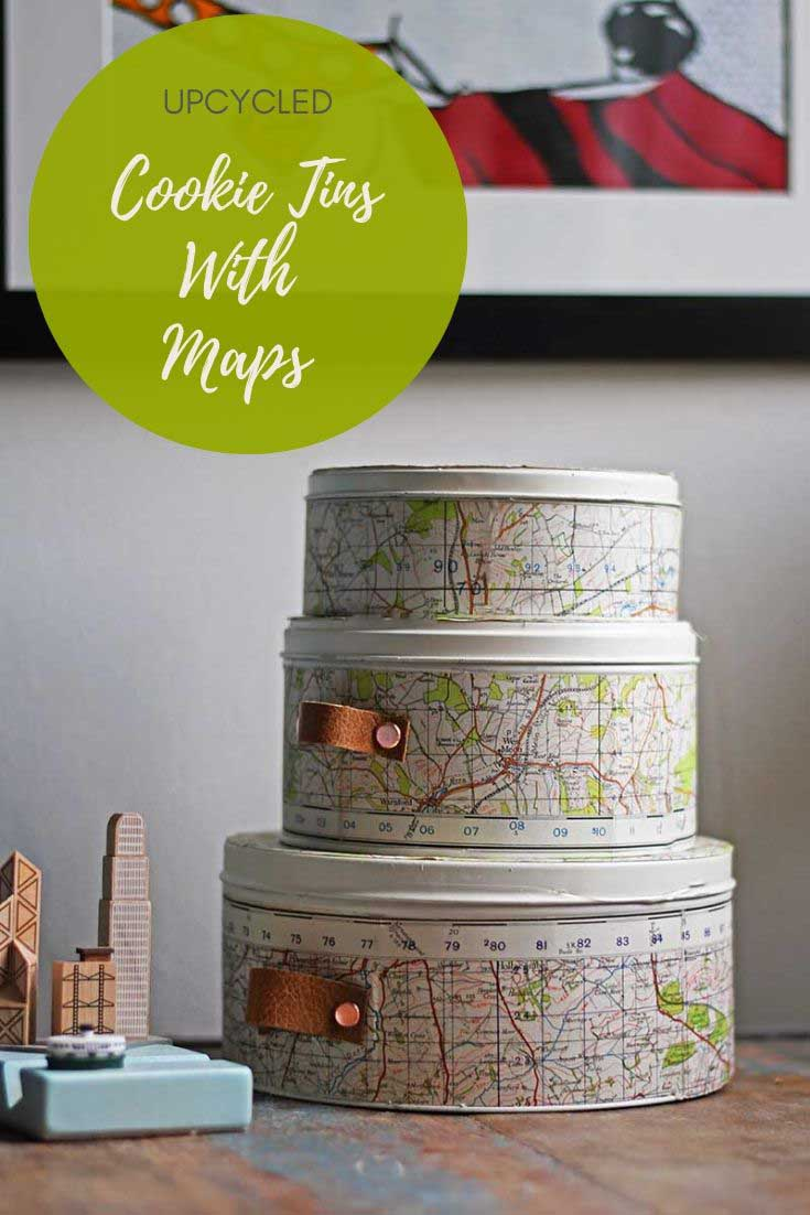 Create some stylish storage by repurposing empty cookie tins with maps and leather handles. These storage tins would look great in any travel themed room. #storage #cookietins #maps #tincans