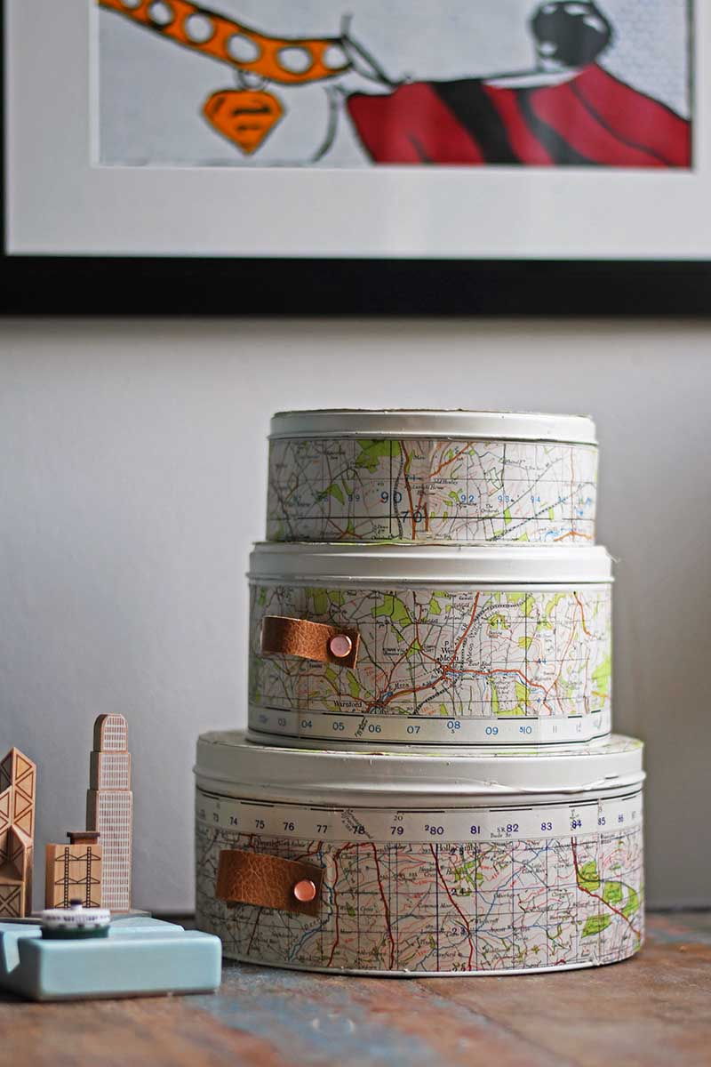 Repurposed empty cookie tins with maps