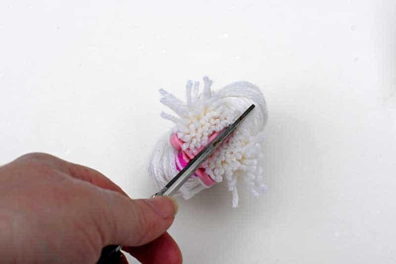 Cutting the yarn on a pom pom maker