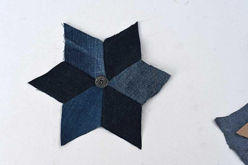 adding a button to upcycled denim quilted stars.