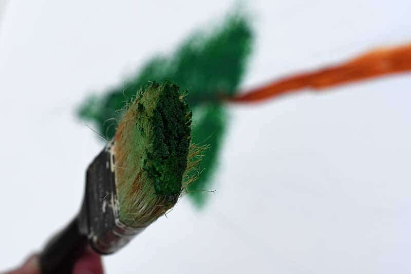 Green paint on the tip of the paint brush.