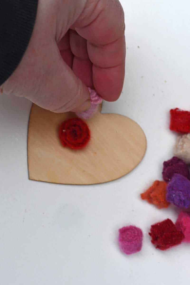 Gluing the felt flowers to the wooden hearts
