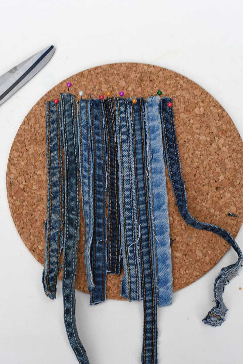 pinning the jeans seams to the cork for weaving